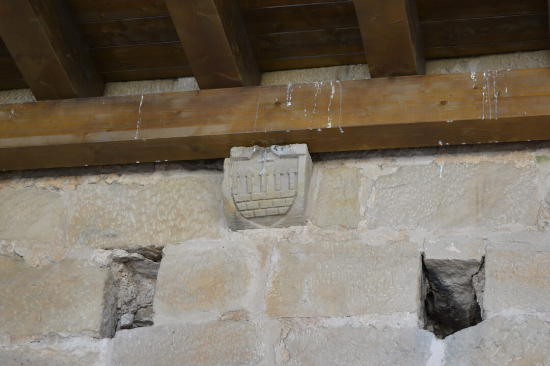 Nou espai de la zona més antiga, del s.XII. Detall d'un escut i forats on estava instal·lat un cadafal de defensa i vigilància.